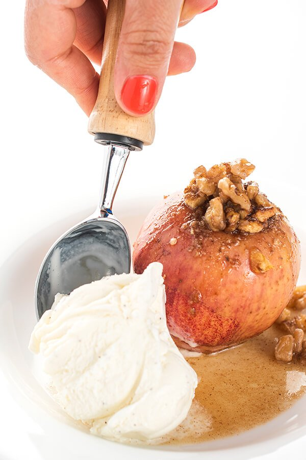 baked apple with walnut topping and with a scoop of ice cream