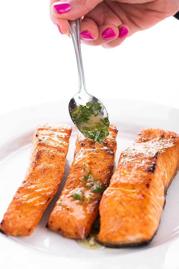 salmon being topped with garnish