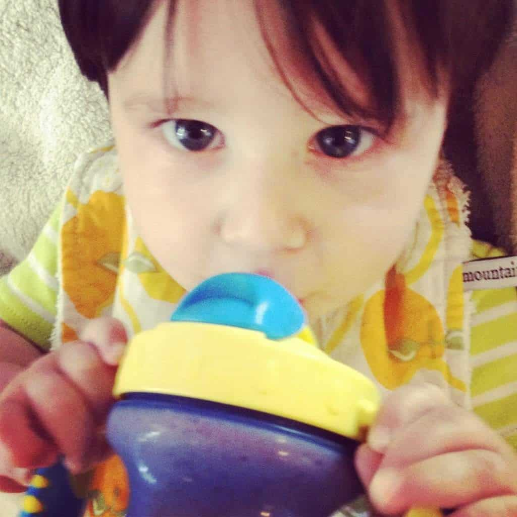 baby with blueberry smoothie