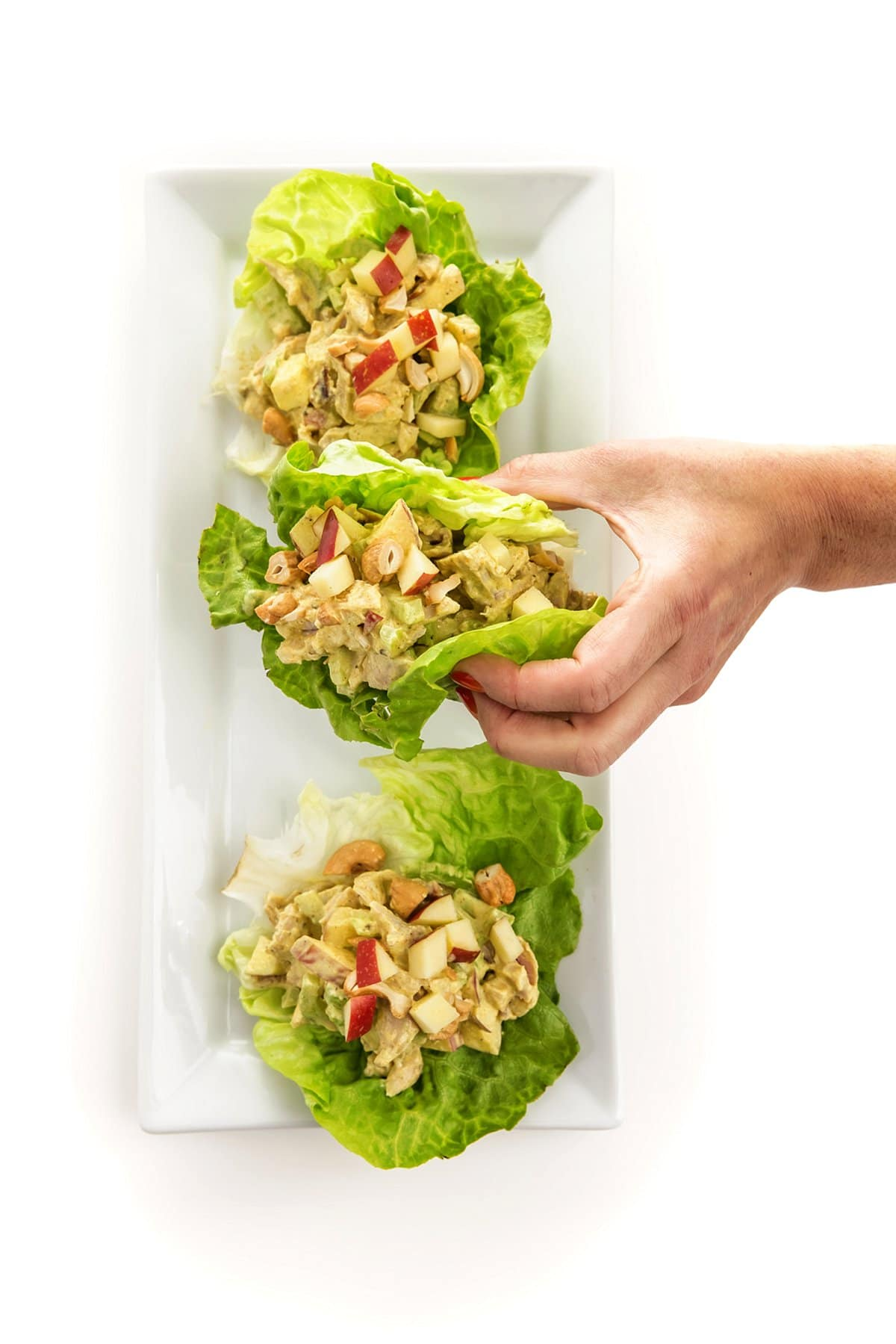 Liz grabbing a lettuce wrap with curried chicken salad with apples