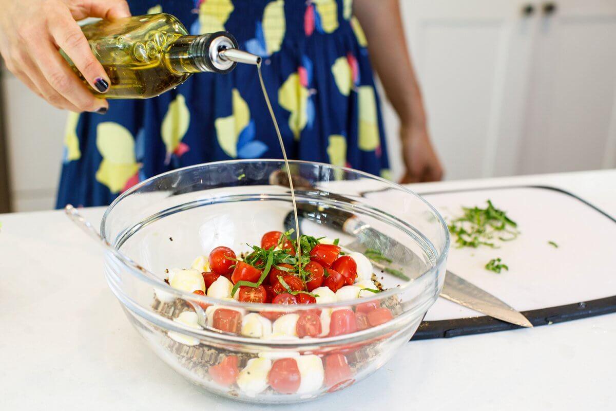Liz pouring olive oil into Caprese Quinoa Salad