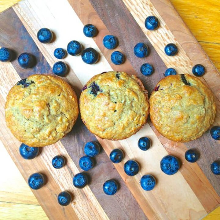 blueberry muffins lined up with blueberries surrounding