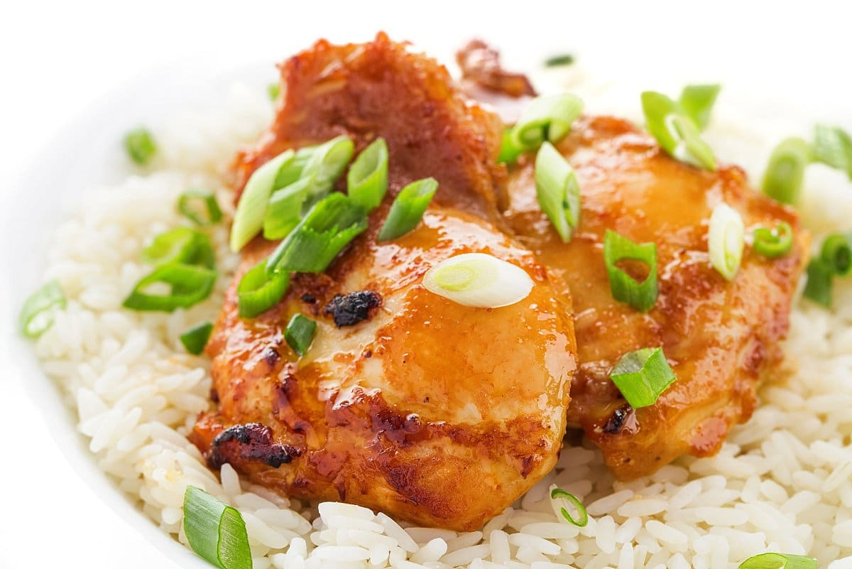 Plated teriyaki baked chicken thighs over rice
