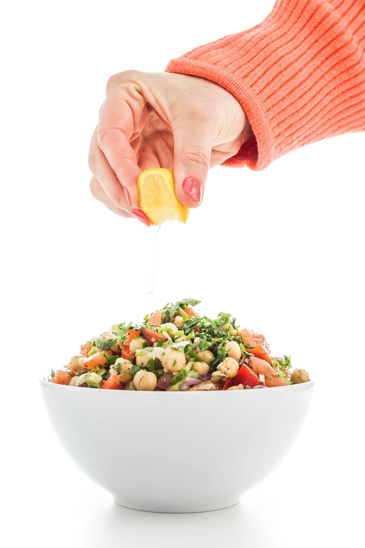 Liz squeezing lemon on chickpea salad