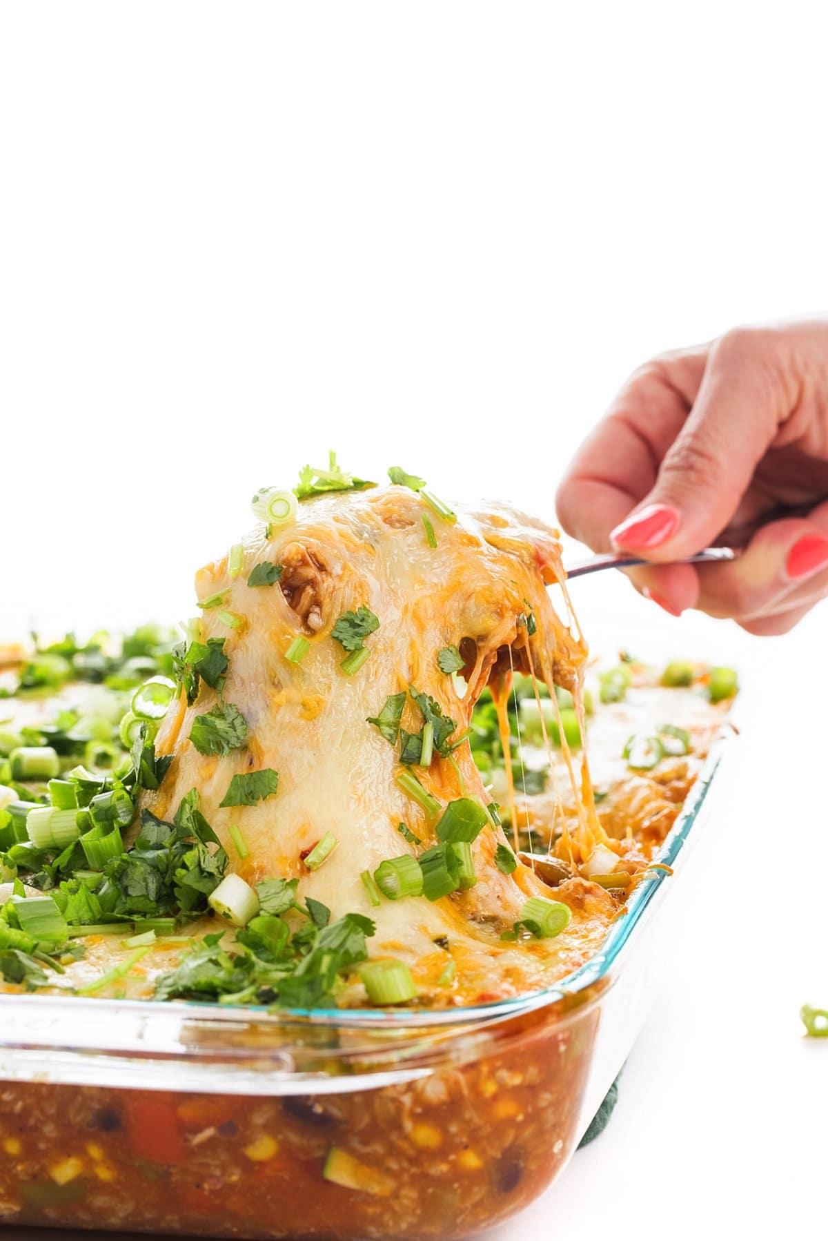 Liz scooping a cheesy bite of chicken enchilada farro bake