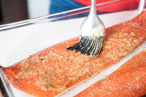 honey mustard being brushed onto salmon