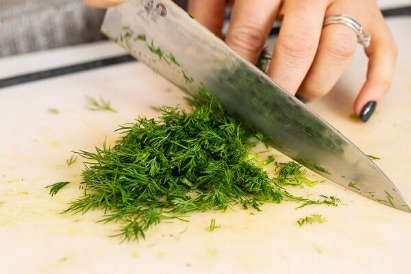 dill being cut with a knife