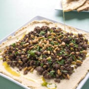 plate of hummus and ground lamb with olive oil being drizzled onto it