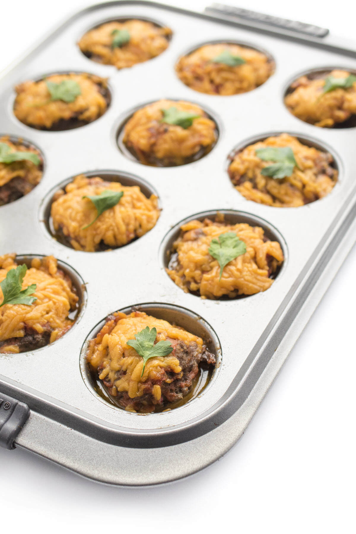 cheeseburger meatloaf muffins in a muffin pan