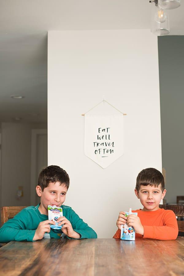 two cute kids enjoying their stonyfield yogurt pouches