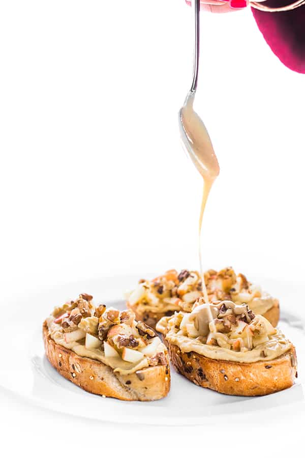 This fresh spin on breakfast toast is topped with creamy hummus, crunchy apples and toasted walnuts then drizzled with a sweet tahini honey sauce.