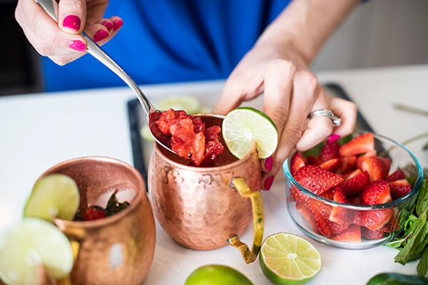 placing strawberries into a copper mule mug