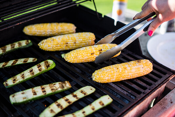 corn being grilled with zucchini