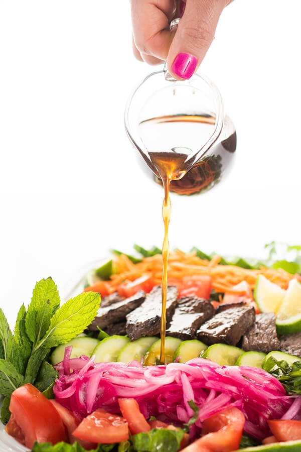 Vietnamese beef salad with marinade being poured onto it