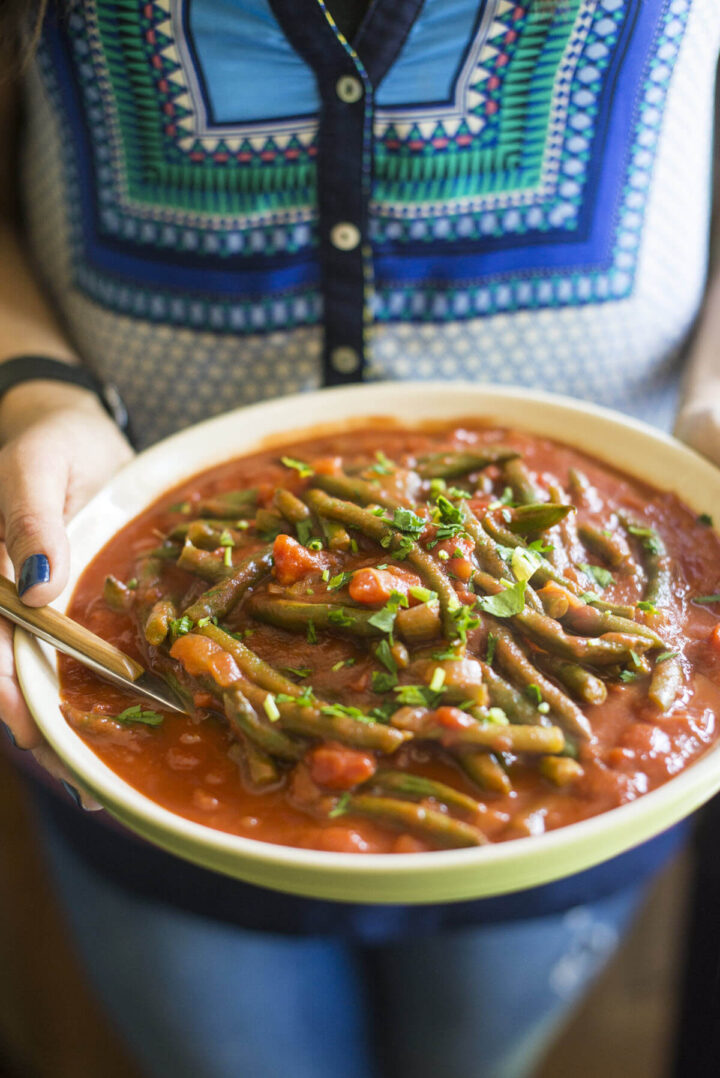 holding a bowl with cooked green beans and tomatoes