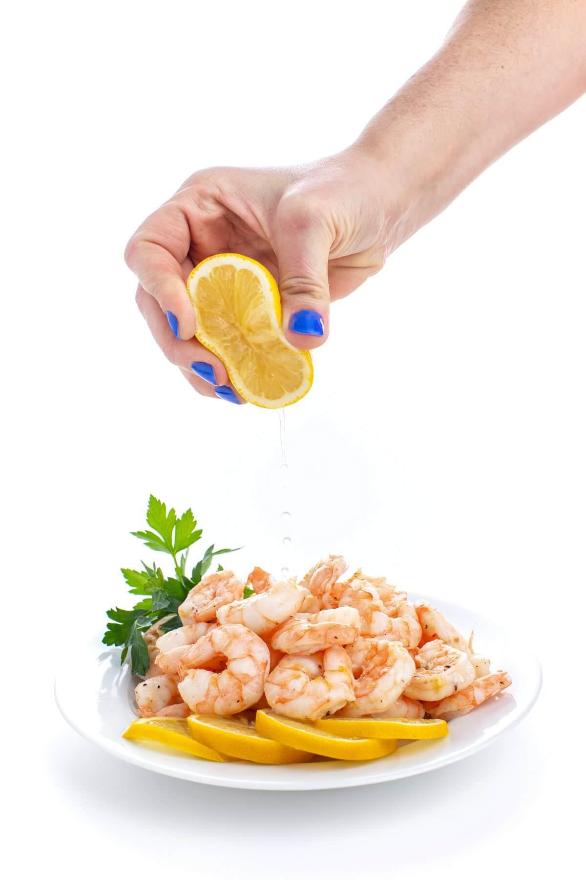 lemon being squeezed onto shrimp