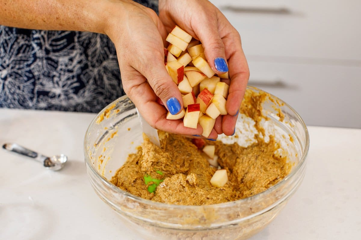Liz's hands cupped full of chunks of apples being poured into the batter for pumpkin applesauce muffins in a glass bowl