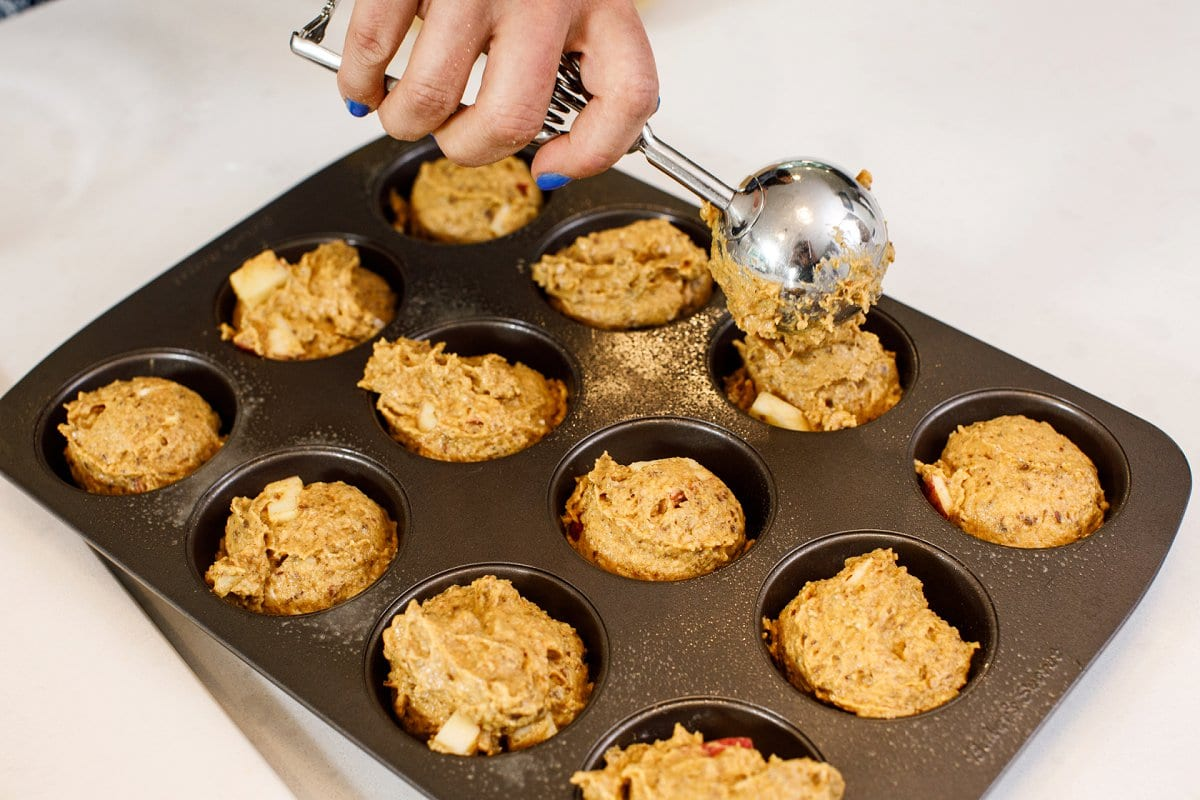 Liz's hand holding a scoop full of pumpkin muffin batter being poured into a muffin tin