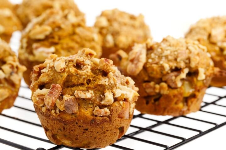 Baked pumpkin applesauce muffins on a wire rack with a white background