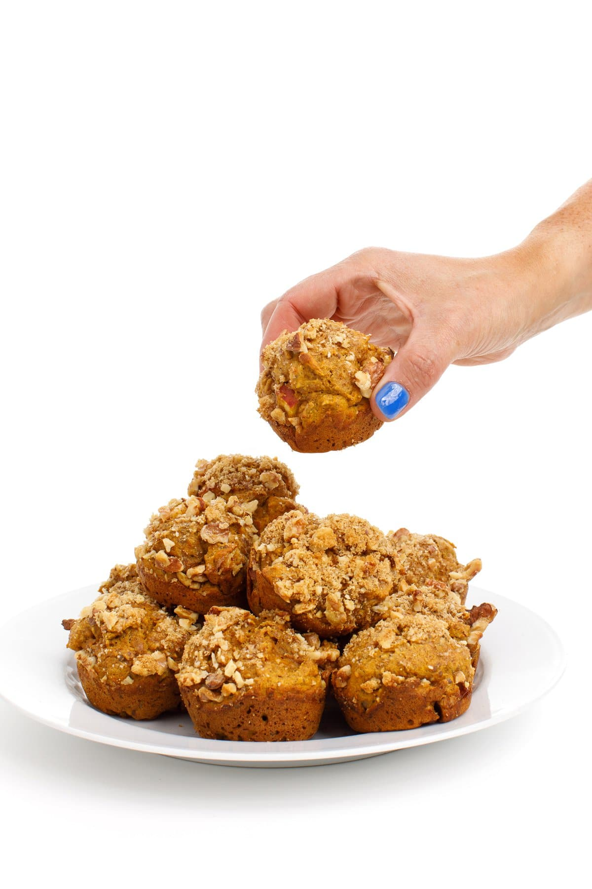 A hand grabbing a pumpkin applesauce muffin from a stack with a white background