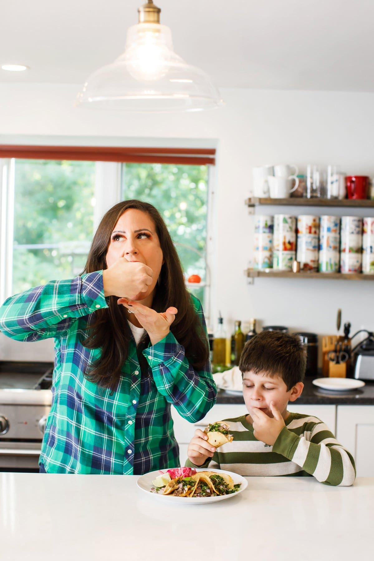 Woman and son eating beef birria tacos