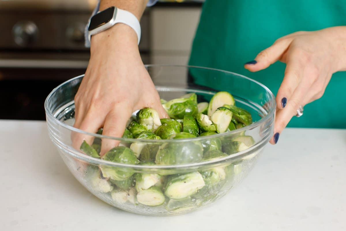 woman mixing Brussels sprouts and seasonings