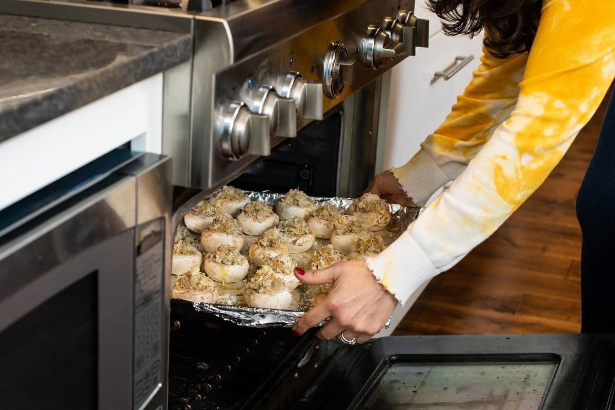 Stuffed mushrooms being placed in oven