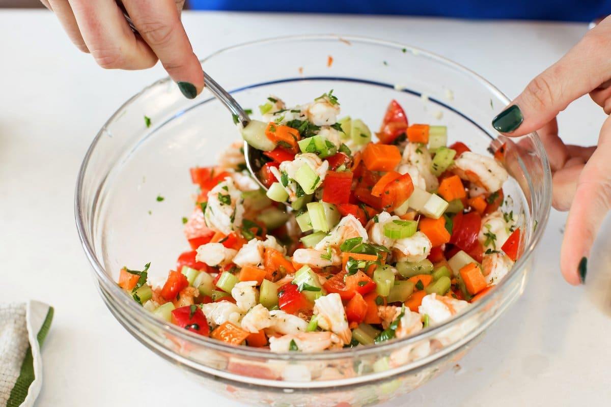 stirring shrimp salad