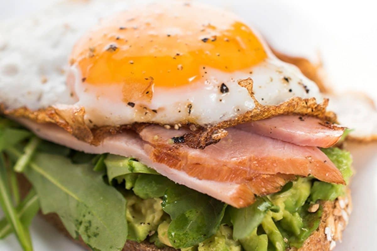 avocado toast with ham, arugula, and egg