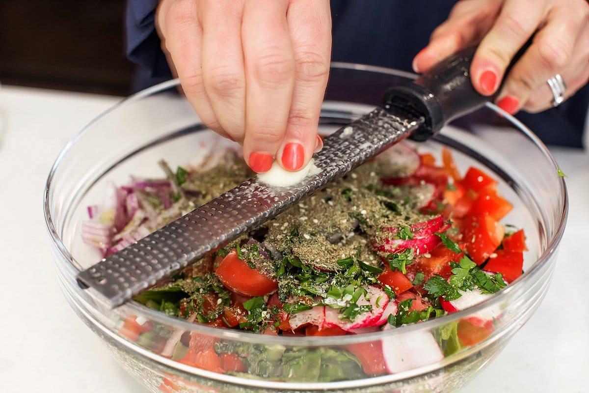 Liz grating garlic over syrian salad