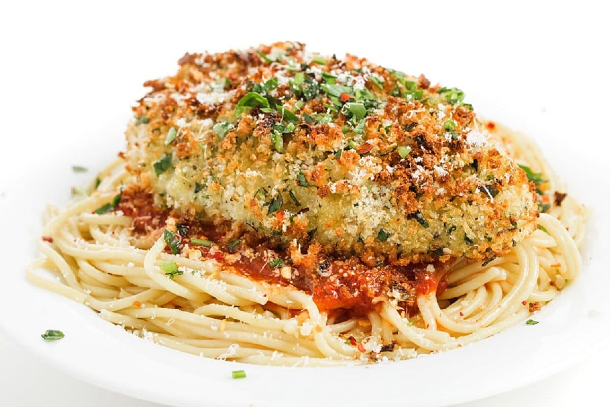 Chicken parmesan plated over pasta and marinara