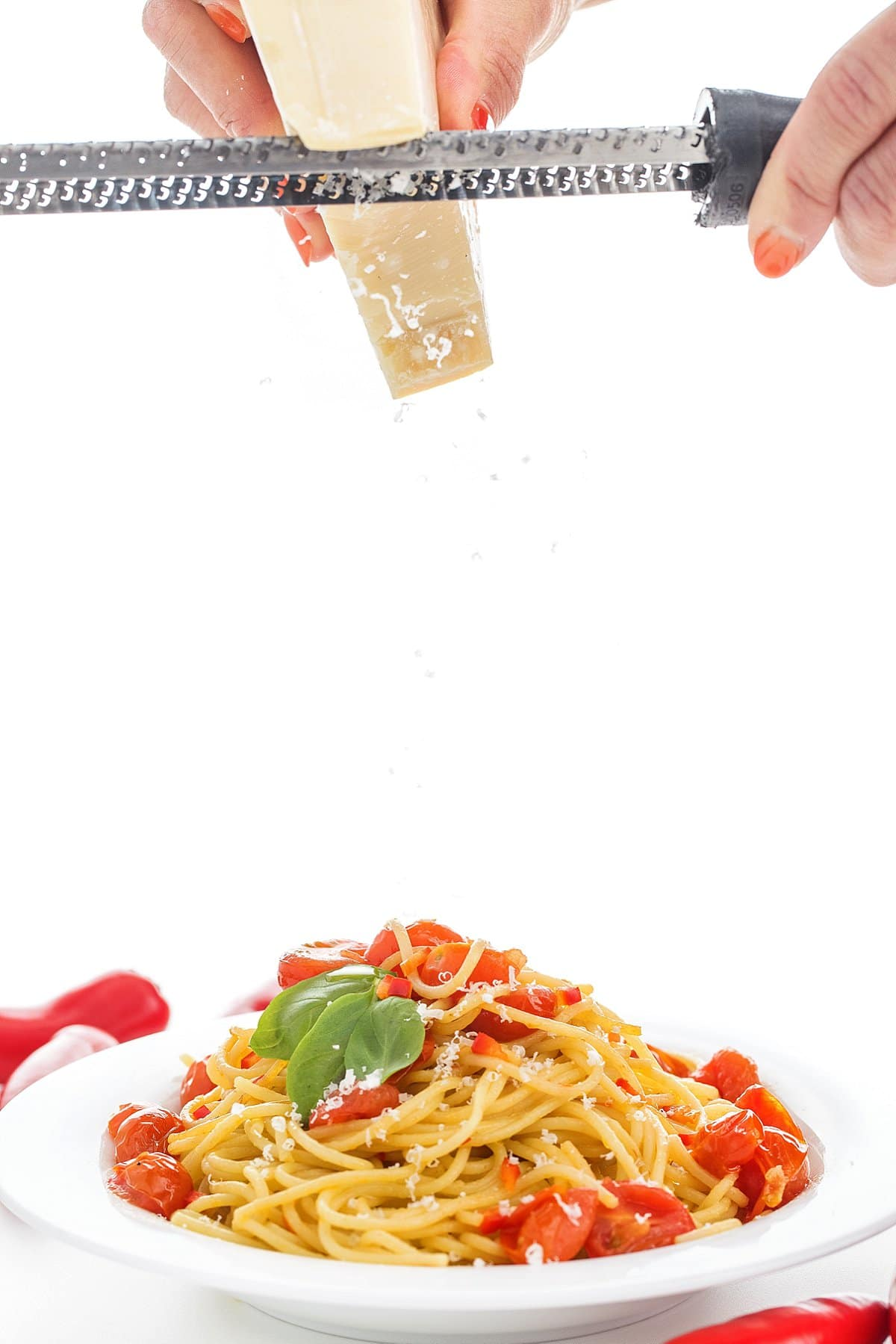 Grating parmesan cheese over spicy pasta with garlic and olive oil