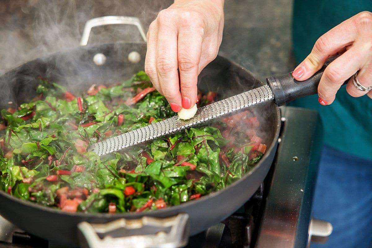 Liz freshly grating garlic into the pan of sautéed swiss chard.