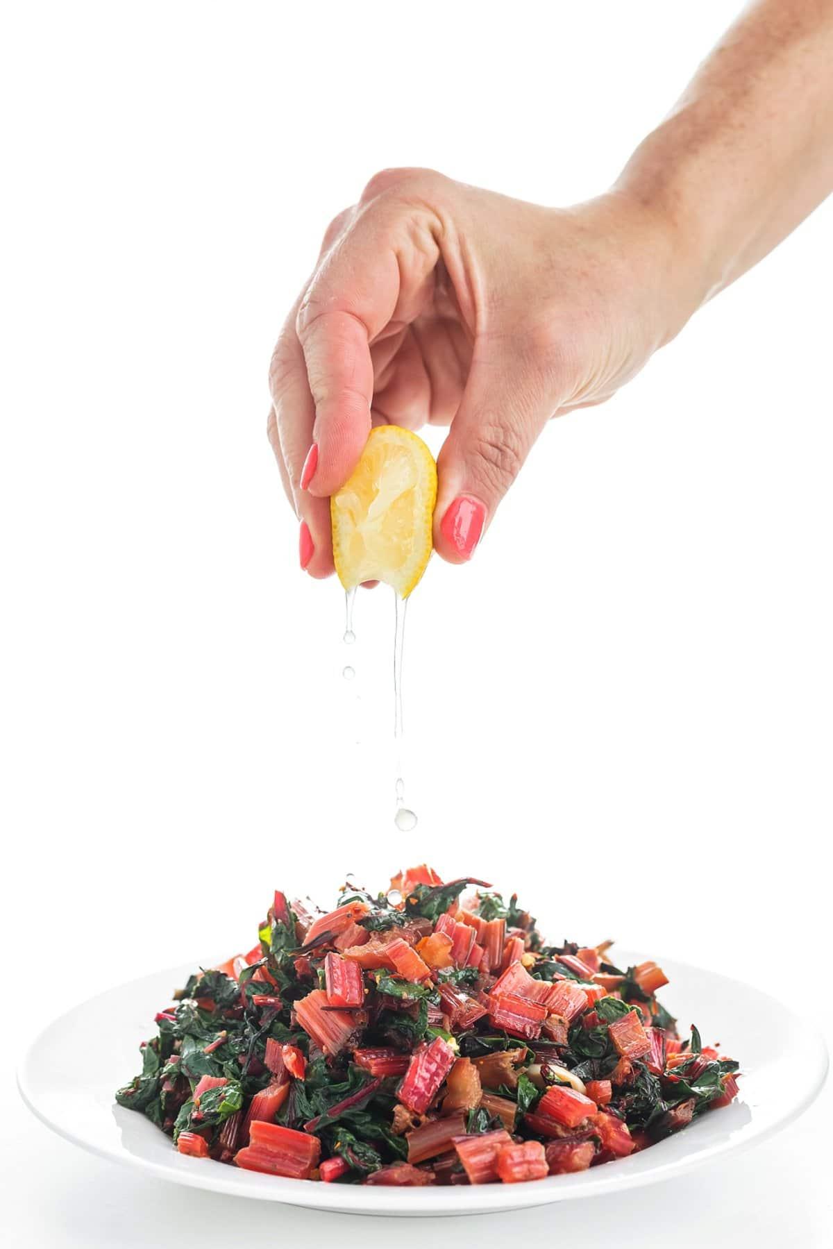 Freshly squeezing lemon juice onto sautéed swiss chard with lemon and garlic.