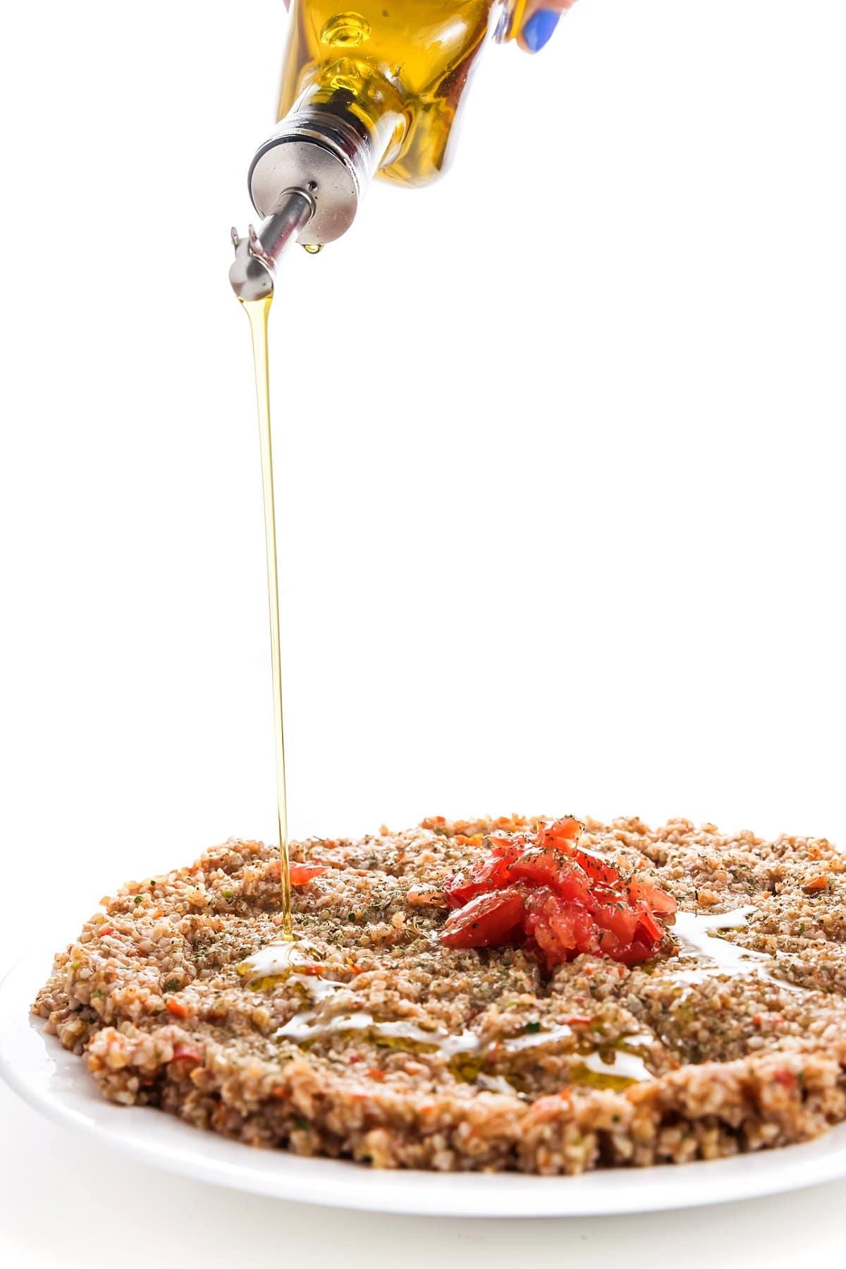 Drizzling oil on vegan tomato kibbeh.