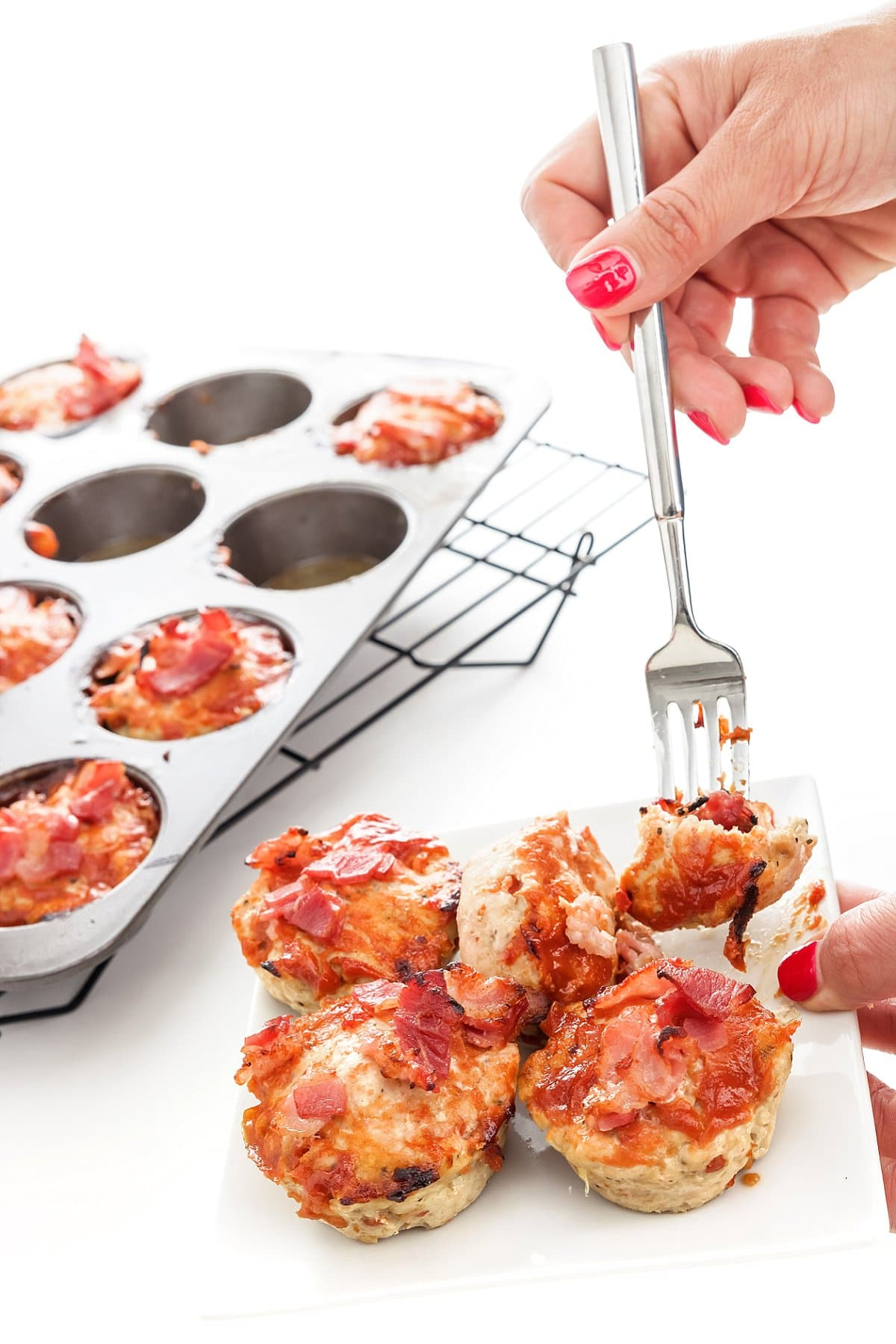 Fork stabbing into turkey meatloaf muffins with bacon.