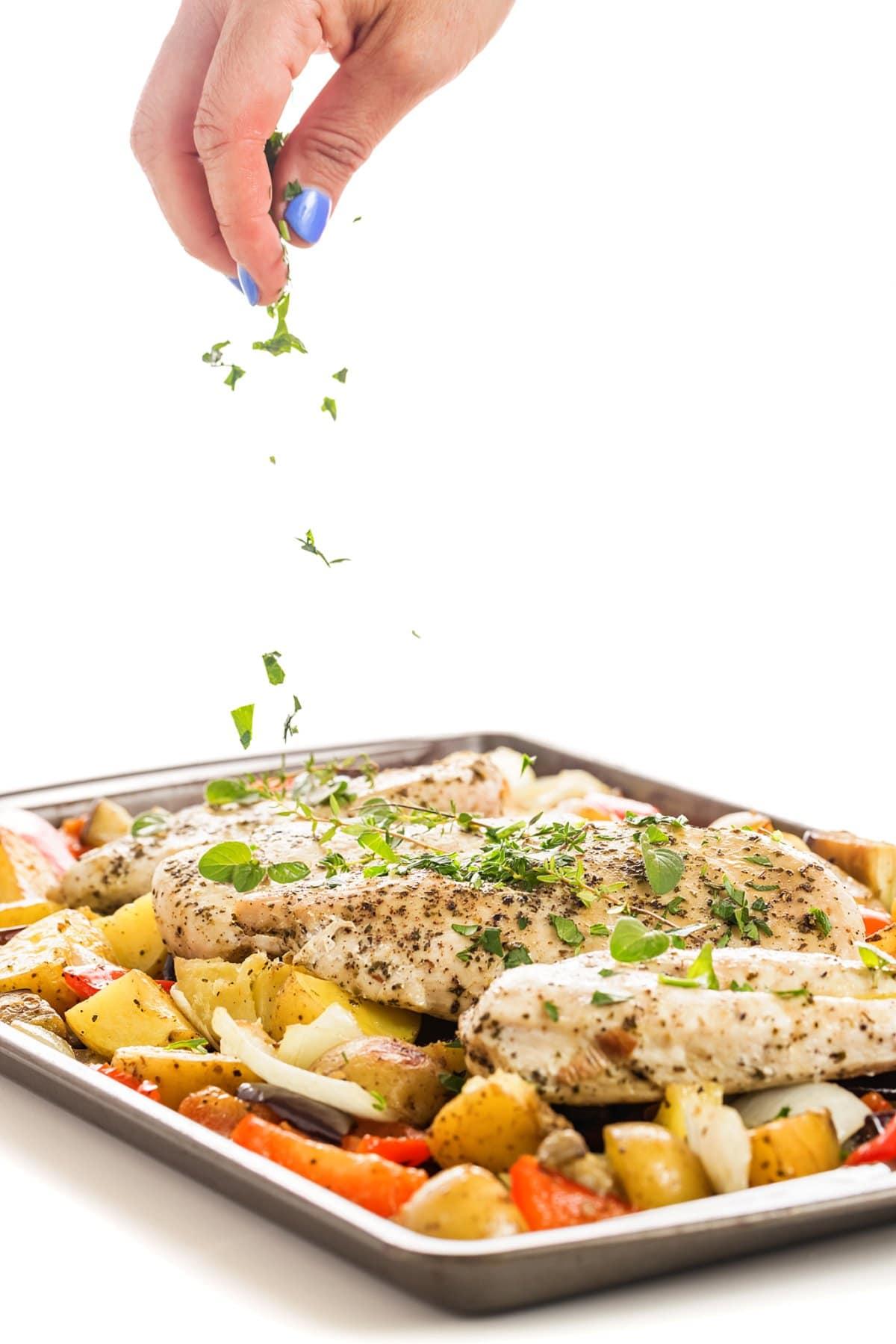 Sprinkling herbs onto sheet pan Greek chicken and vegetables.