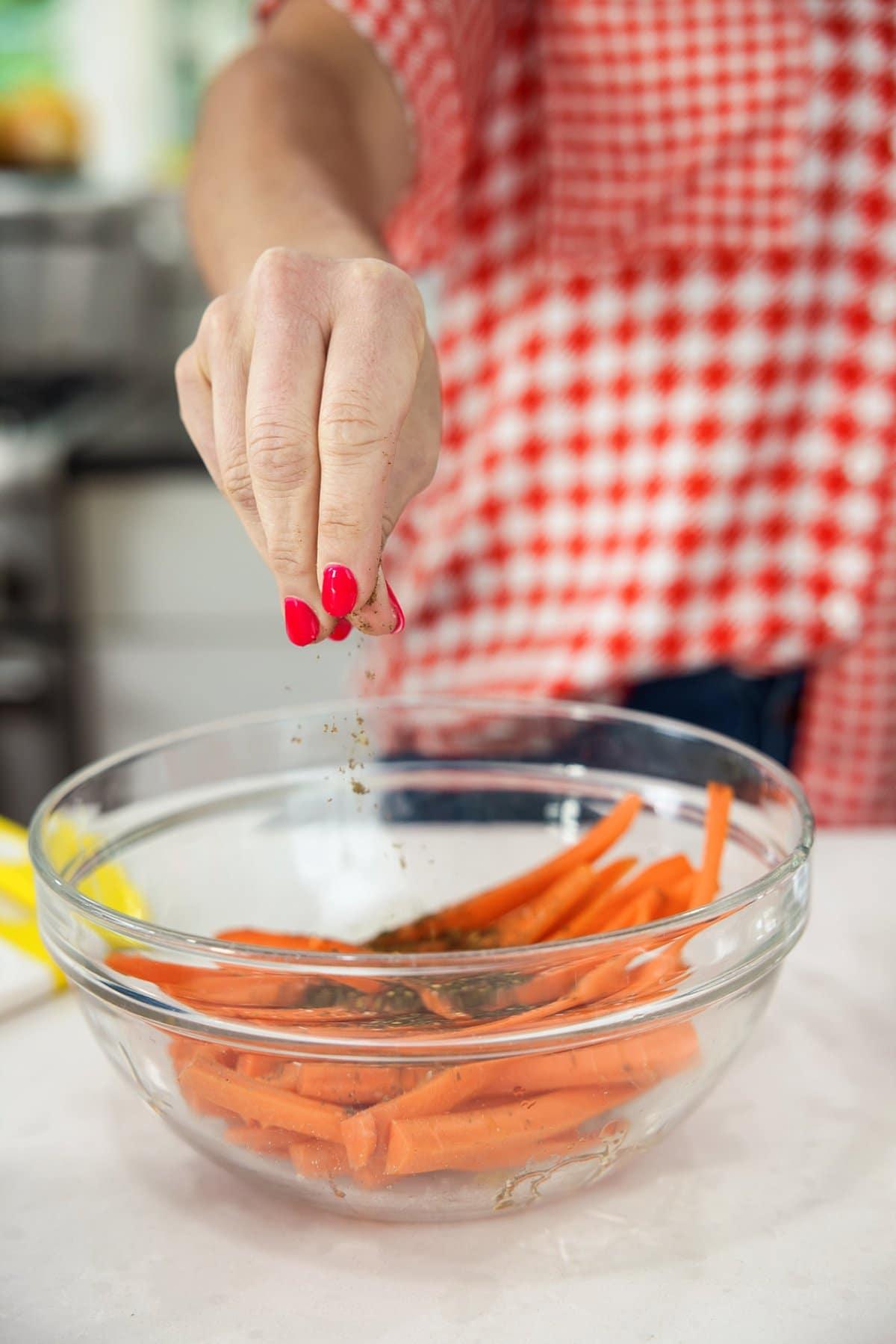 Liz sprinkling za'atar on carrots.