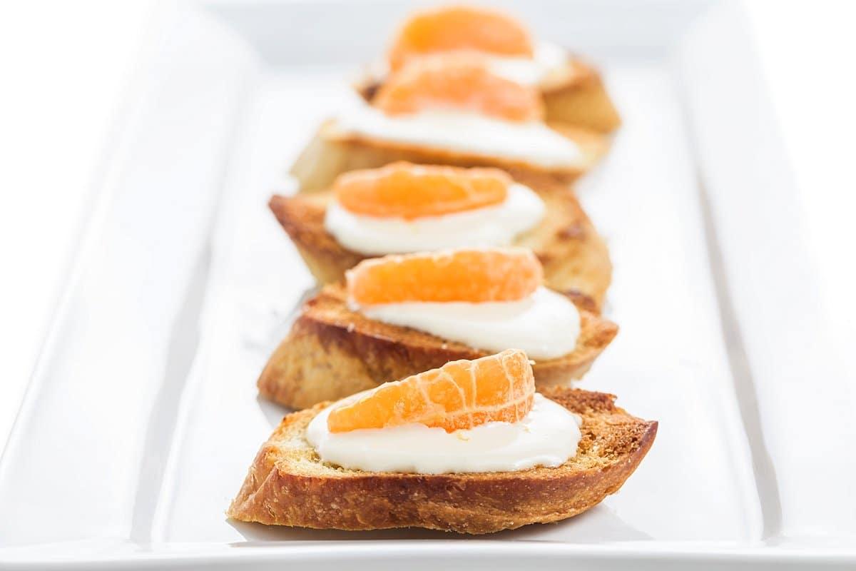 Plate of honey tangerine goat cheese crostini.