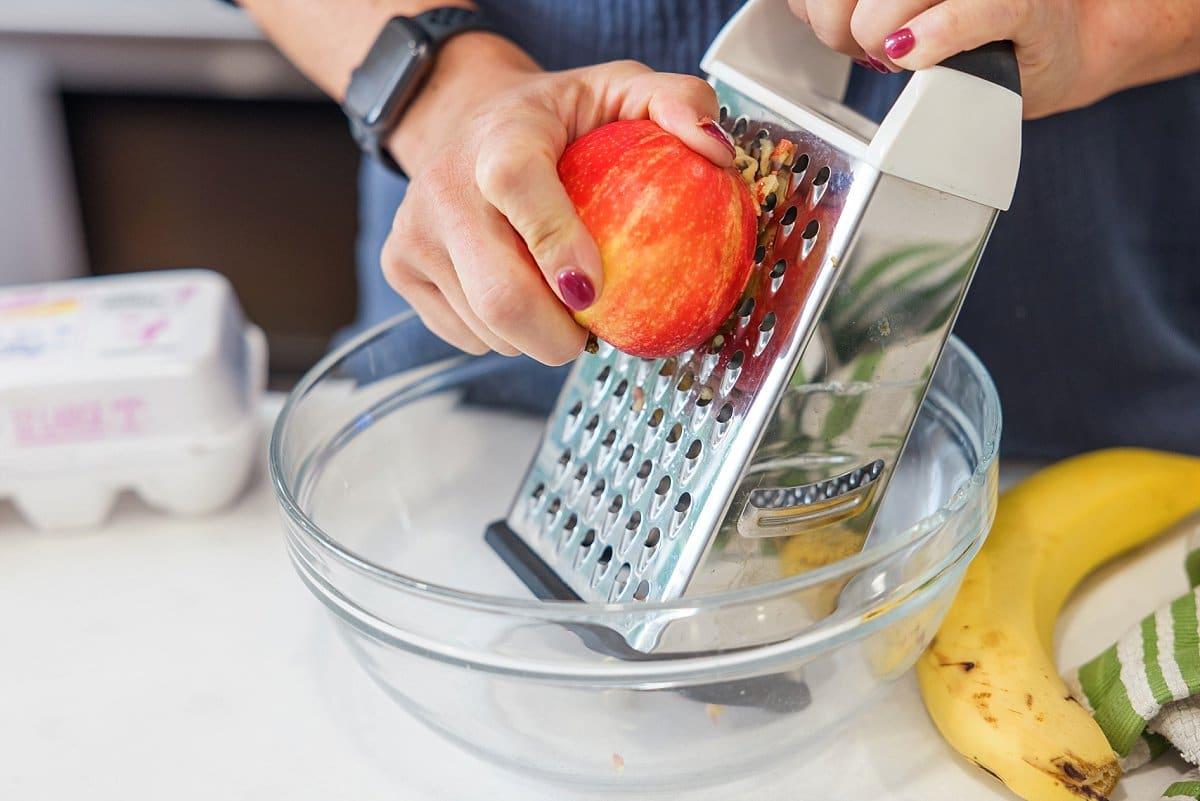 Liz grating an apple.